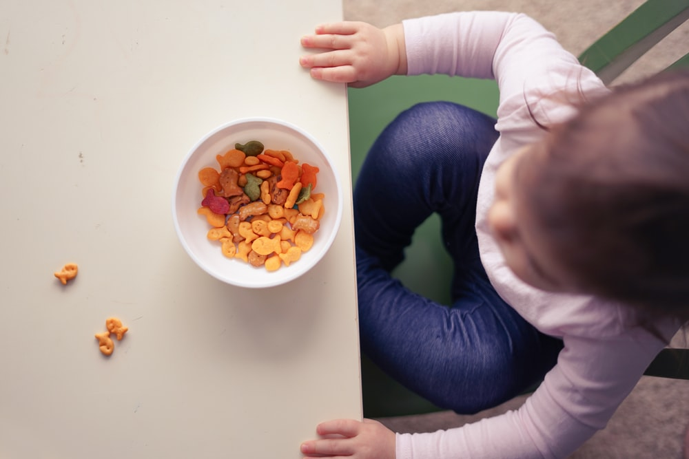 toddler sitting in front of bowl on top of table