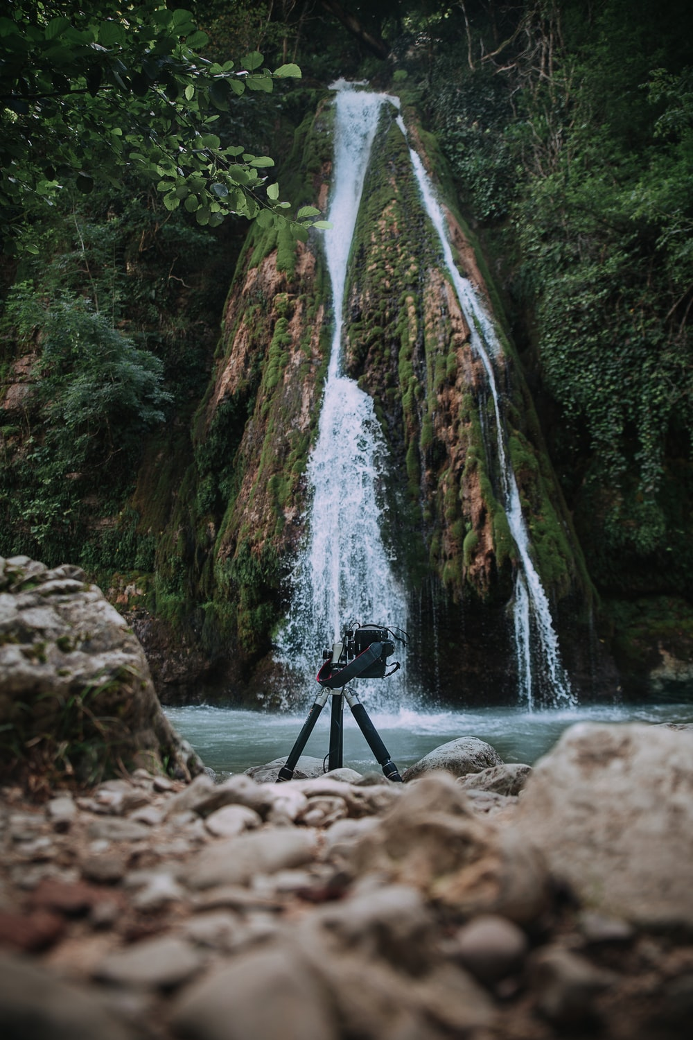 tripod on rocky shore with waterfall background
