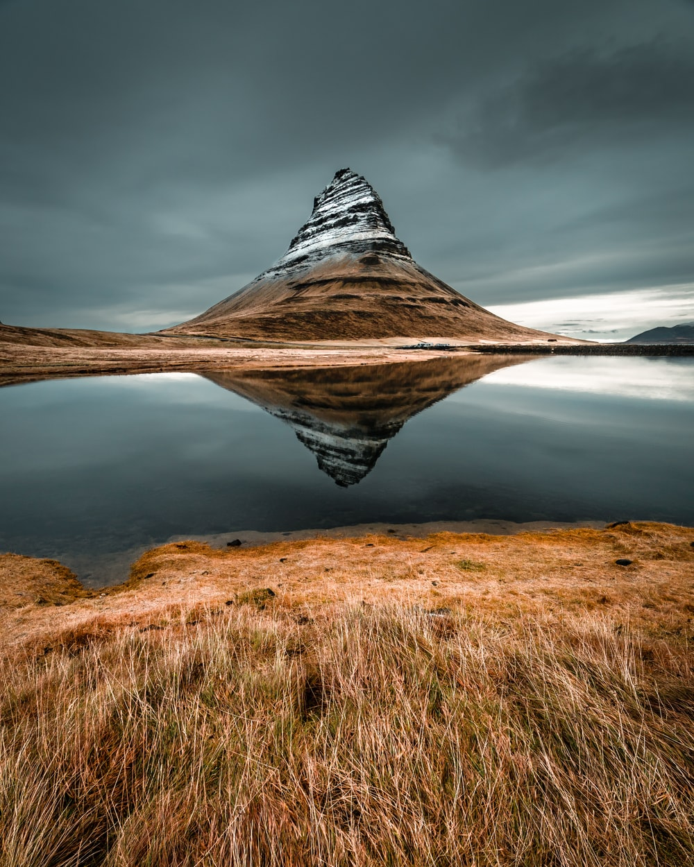 cone mountain with the distance of body of water