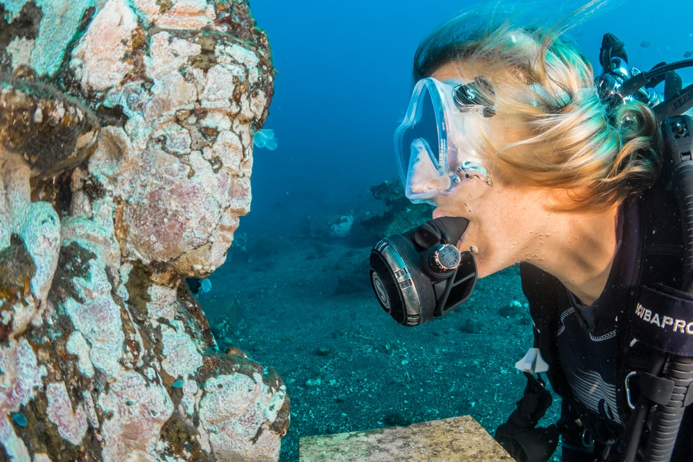 man underwater looking at religious statue