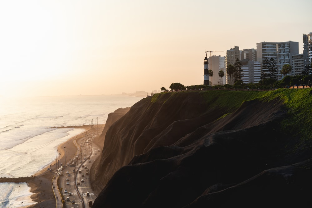 buildings beside cliff and beach