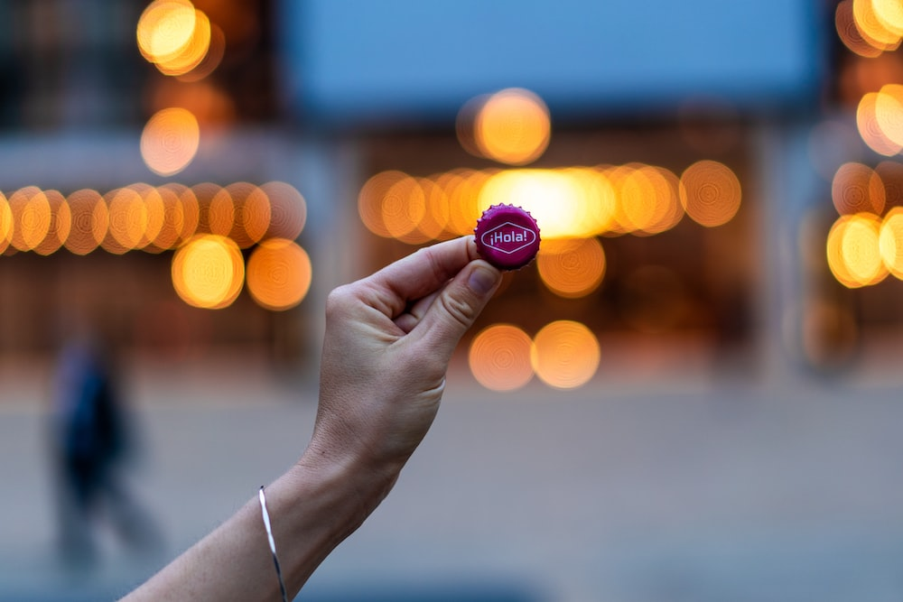 person holding purple bottle lid with bokeh background