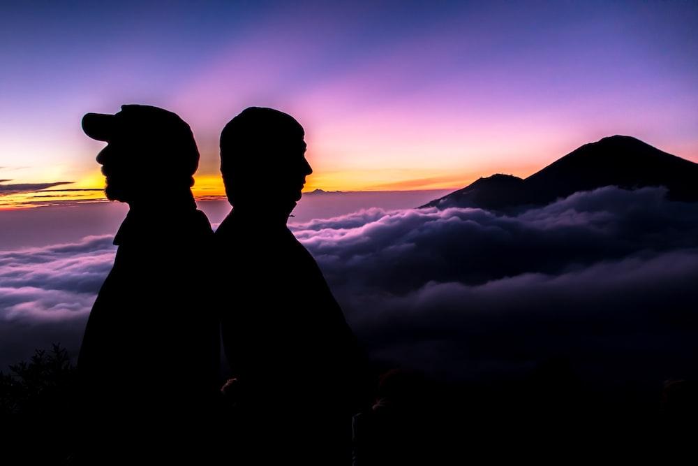 silhouette of men near clouds