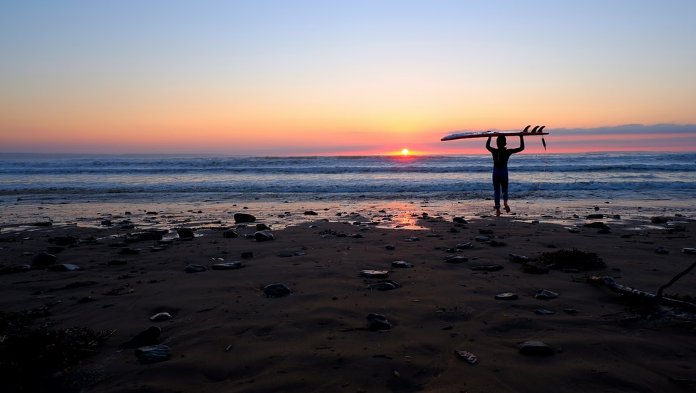 silhouette of person carrying surfboard