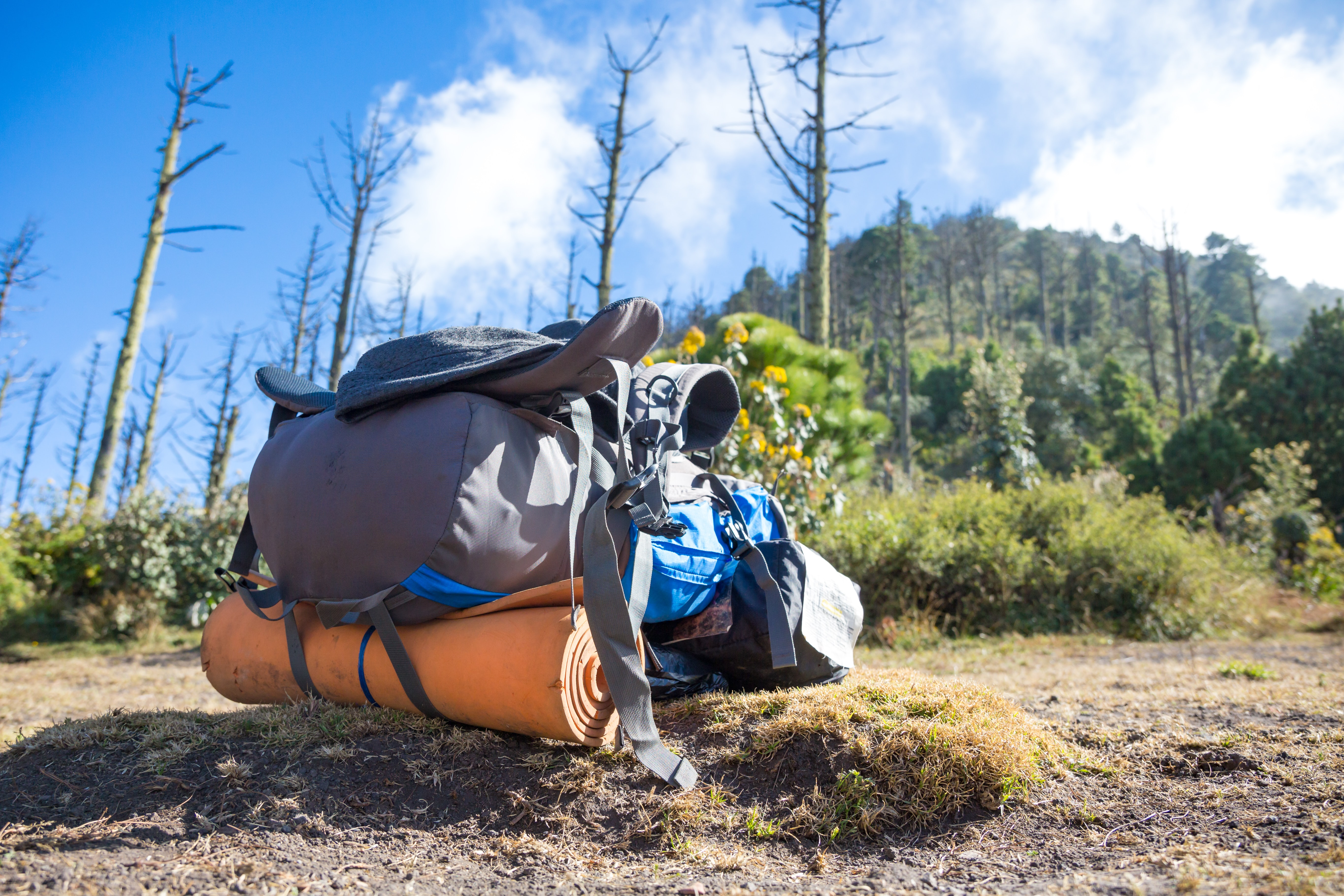 gray, blue, and black hiking backpack on ground overlooking mountain