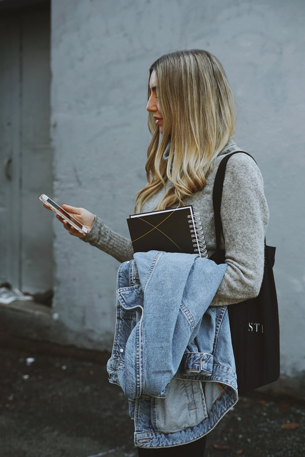 woman holding denim jacket and phone
