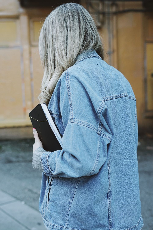 woman wearing blue denim jacket holding black book