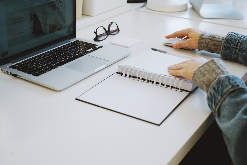 person touching white spiral notebook