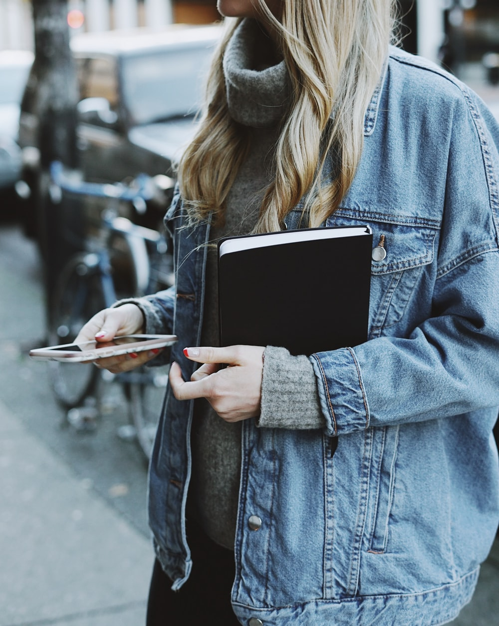 woman standing on sidewalk while holding book and smartphone