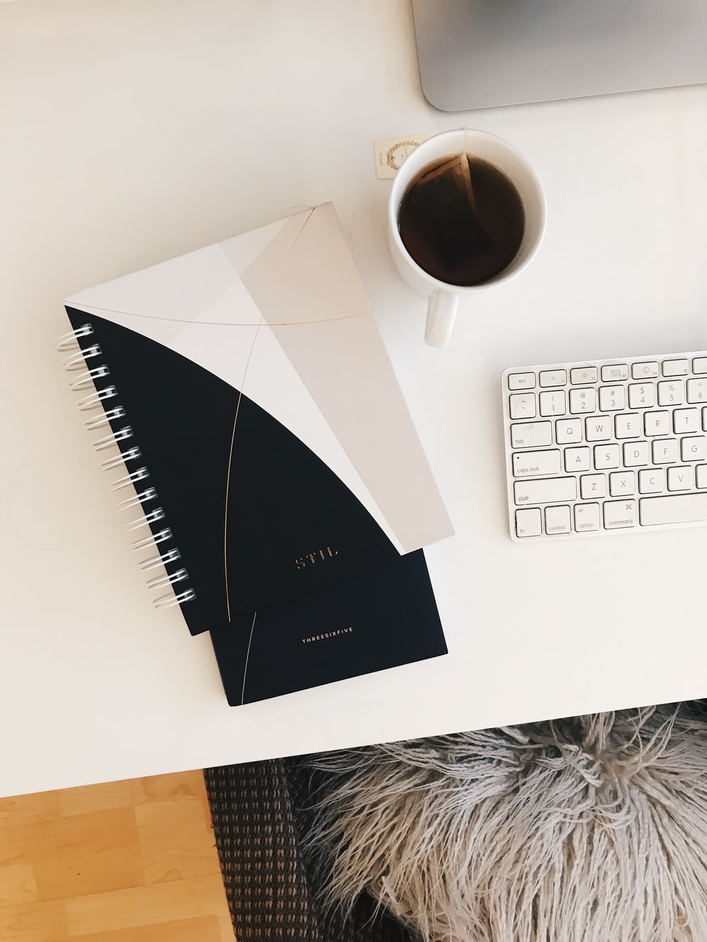 white and black spiral notebook near white teacup filled with black liquid