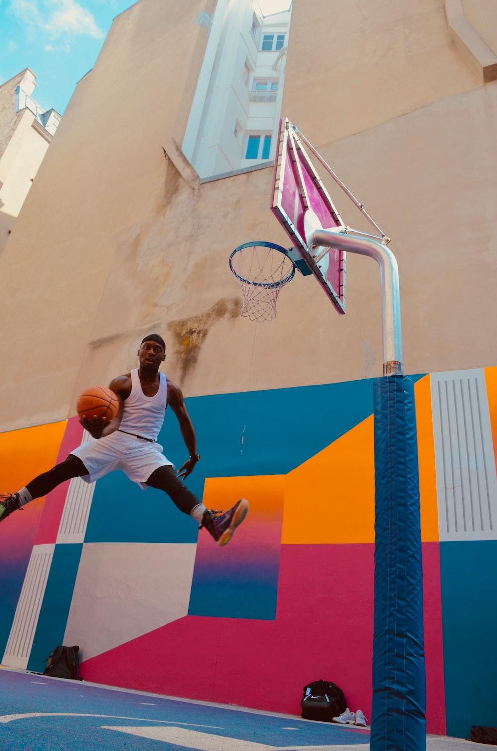 man holding basket ball near concrete building