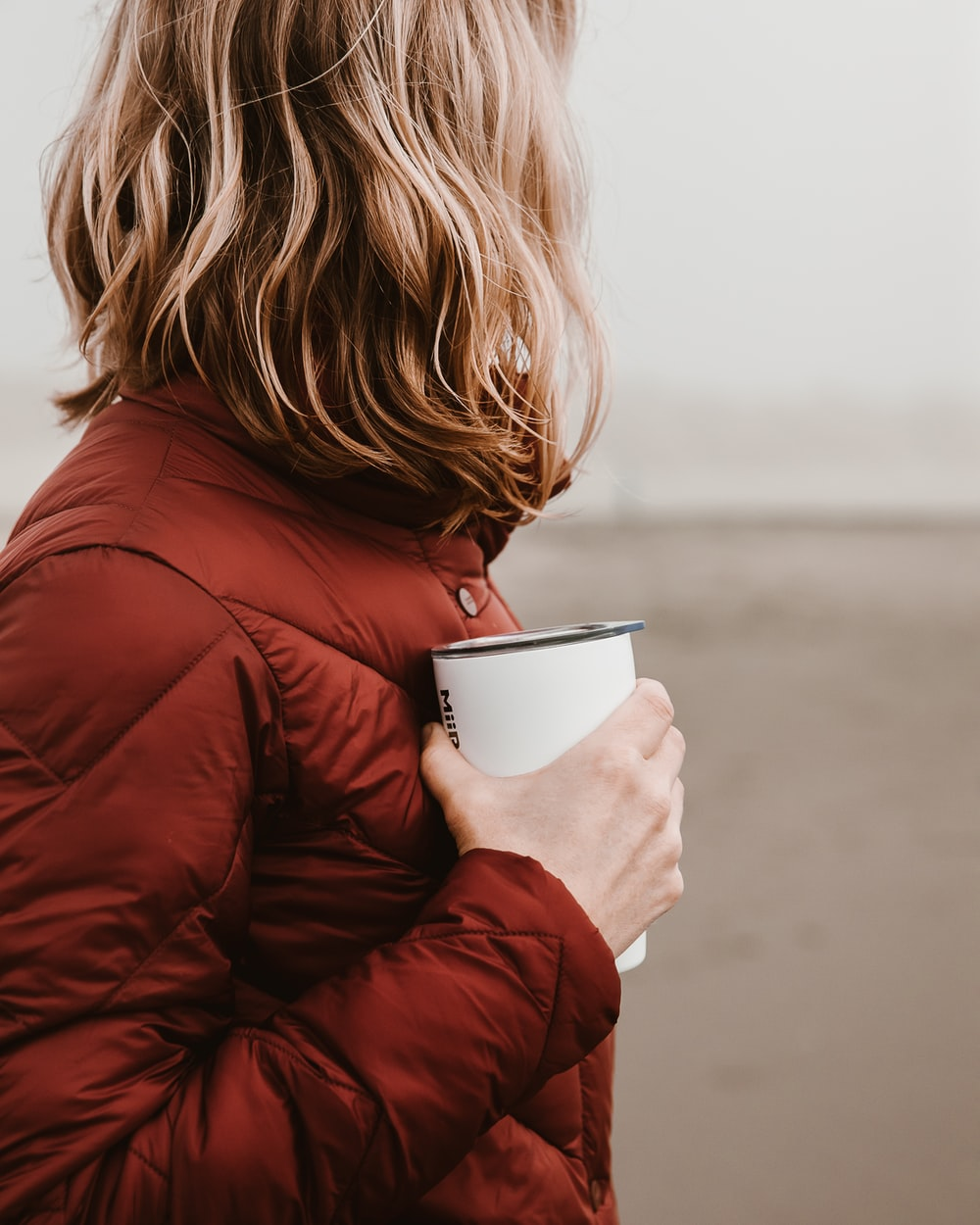 woman wearing brown bubble jacket holding white disposable cup
