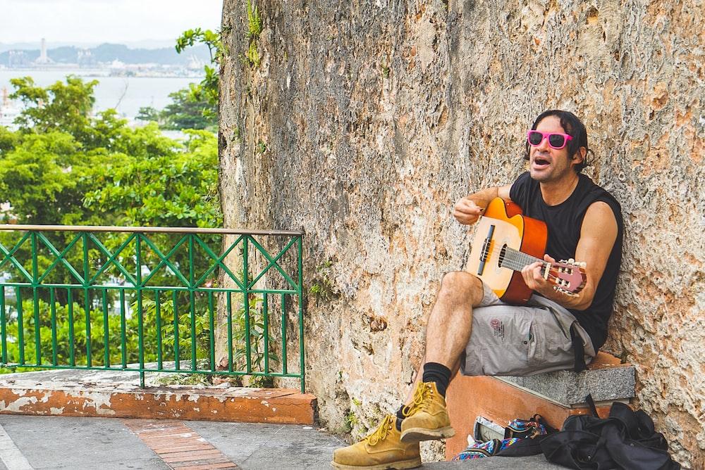 man playing guitar during daytime