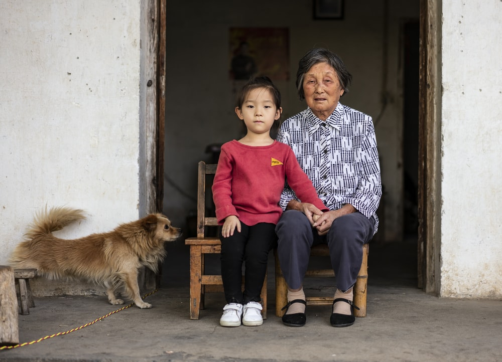 girl and woman sitting near brown dog