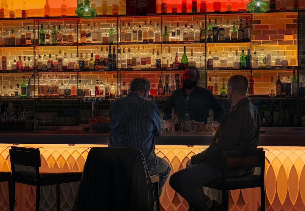 two man sitting on bar stool near table