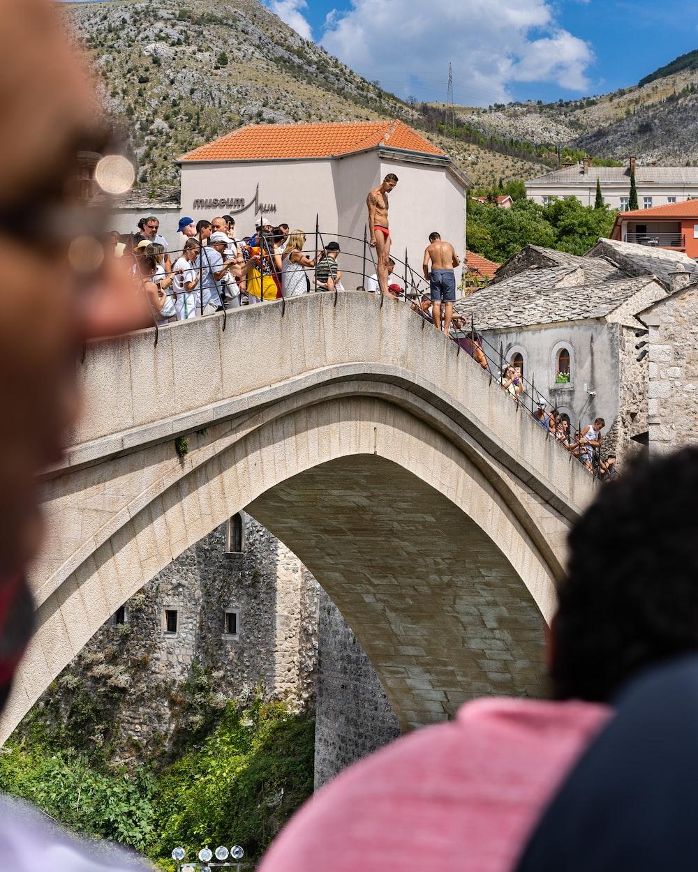 people walking on arch bridge during daytime