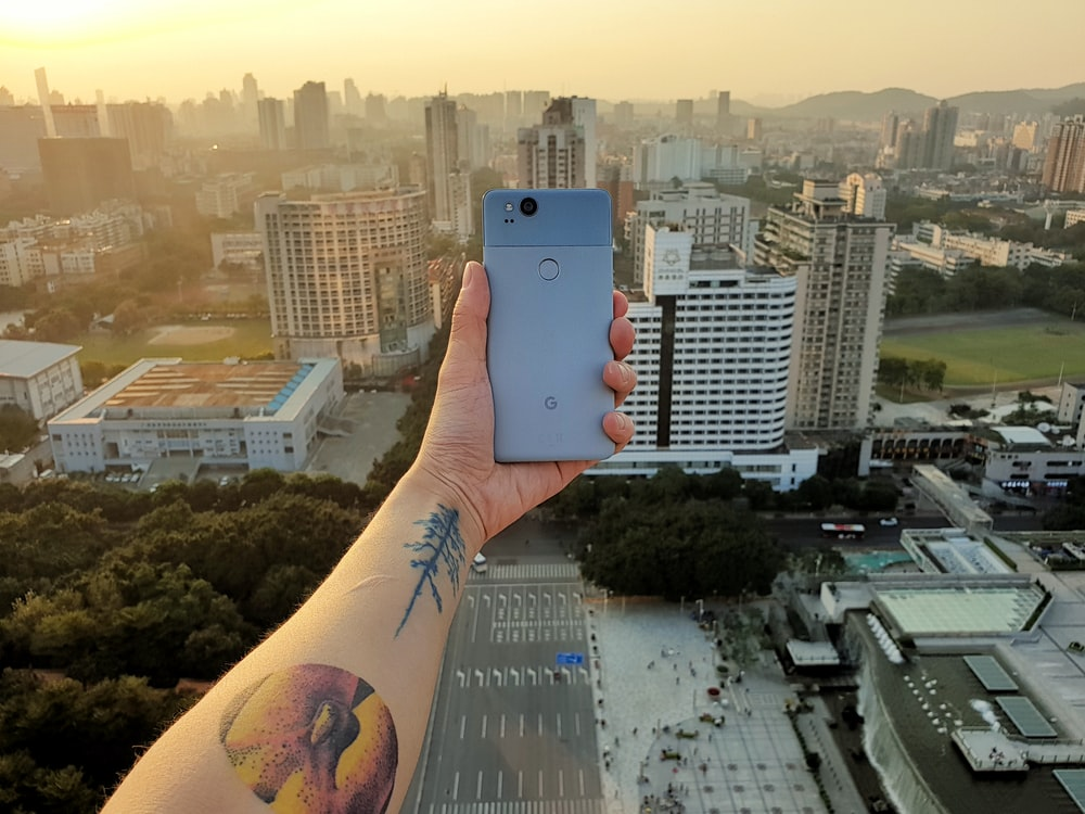 person showing grey smartphone with high rise building view