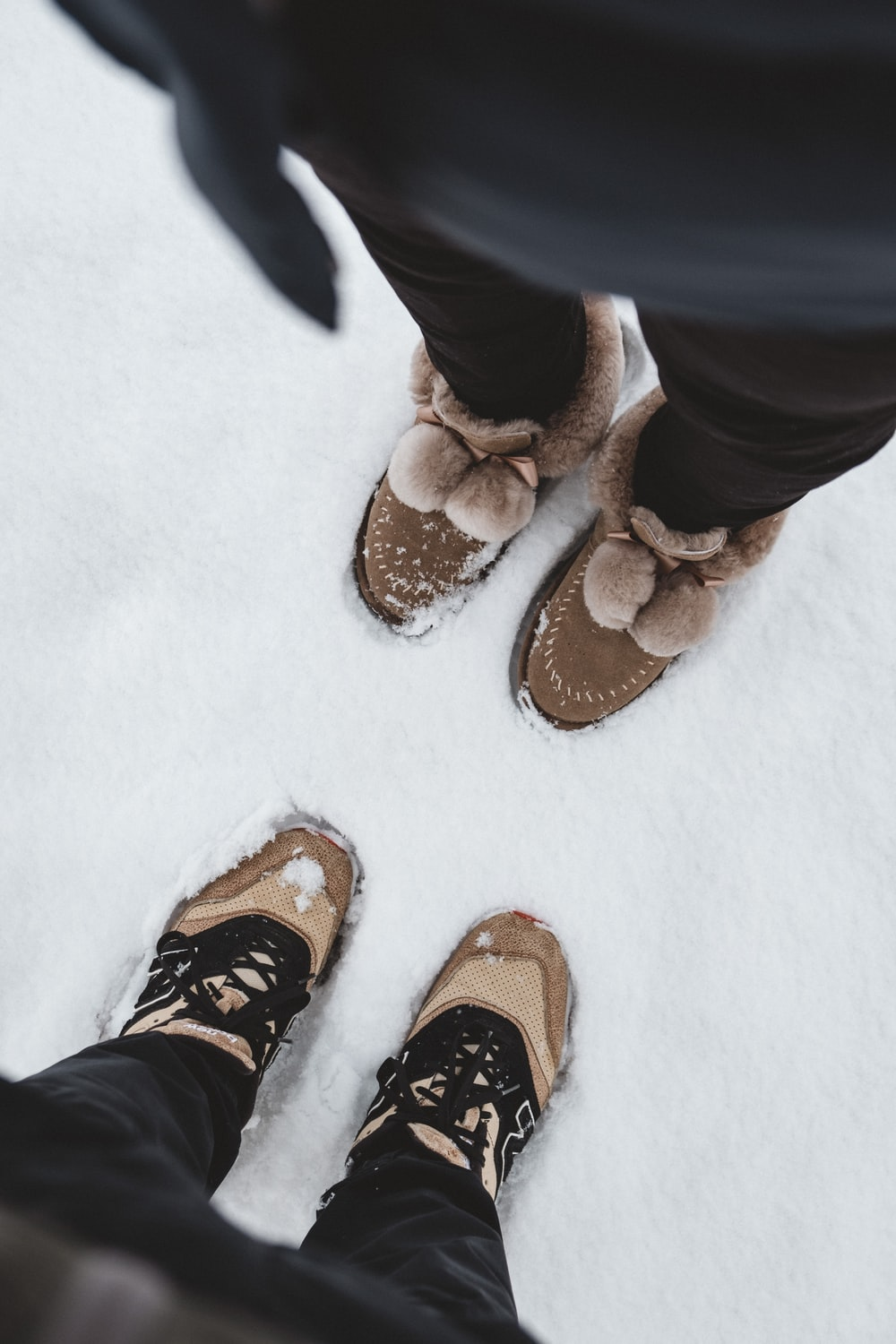 two people standing on snow field