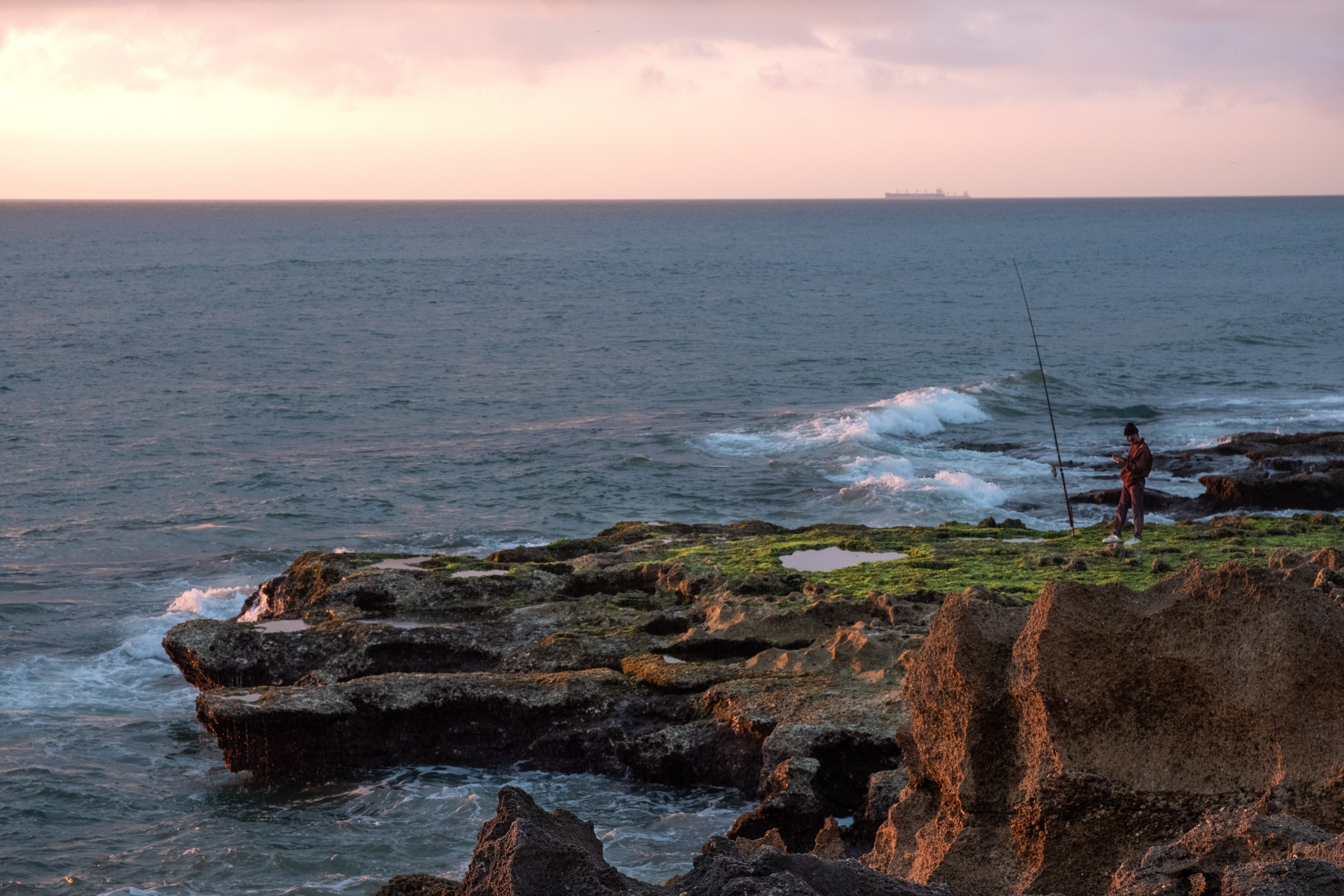 man standing near the edge of a cliff during sunset
