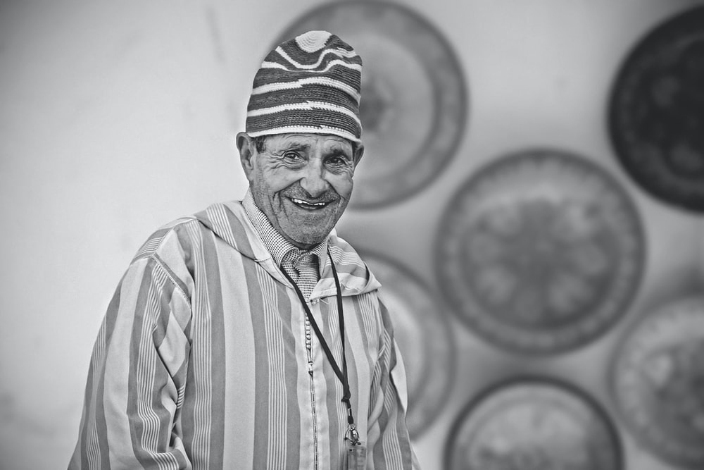 greyscale photo of smiling man wearing dress shirt