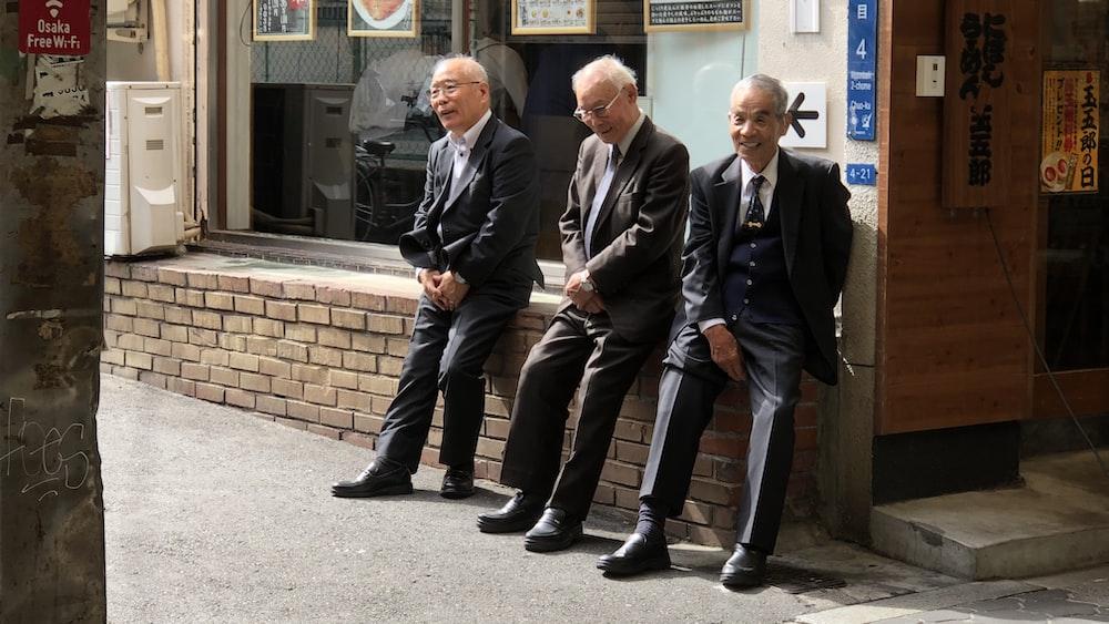 three man in black tuxedo sitting on concrete floor
