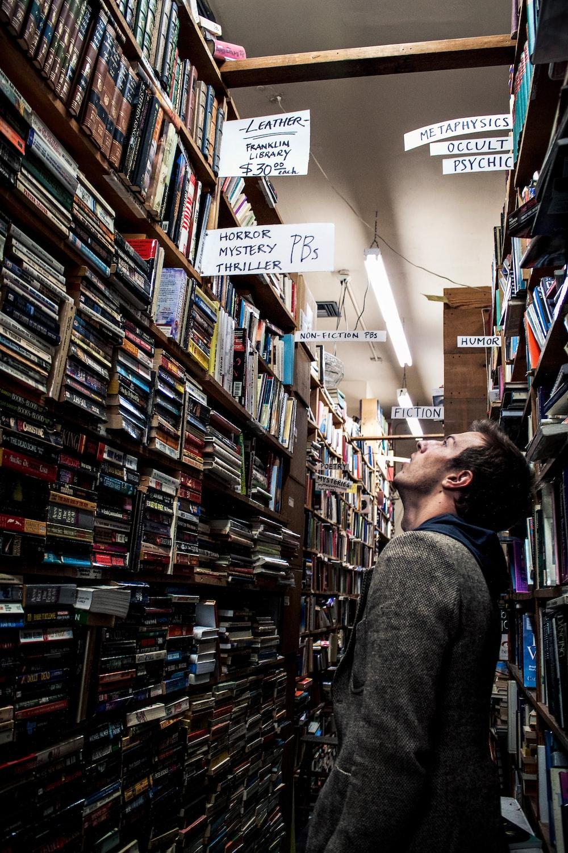 man standing beside book shelf