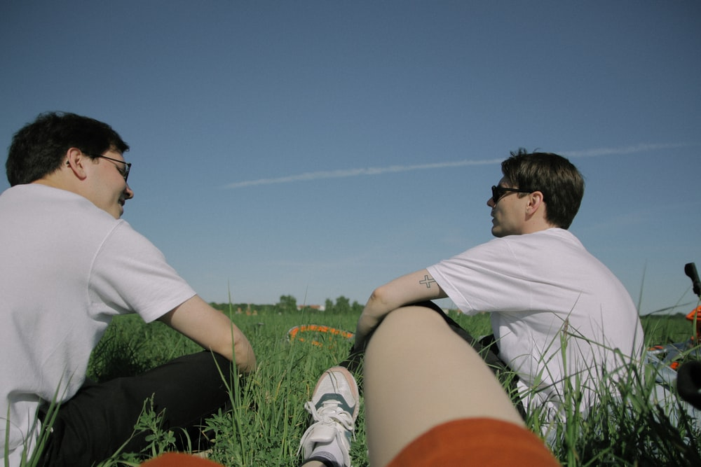 two man wearing white shirts sitting on green ground