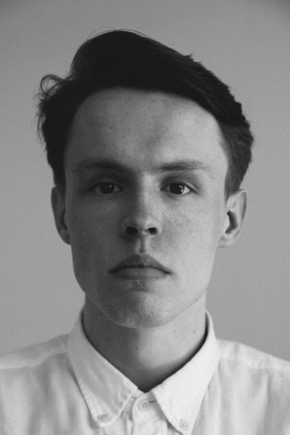 grayscale photography of man wearing collar top