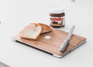 sliced bread on MacBook beside Nutella chocolate bottle