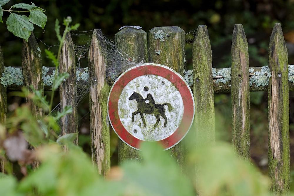 man riding horse signage on fence