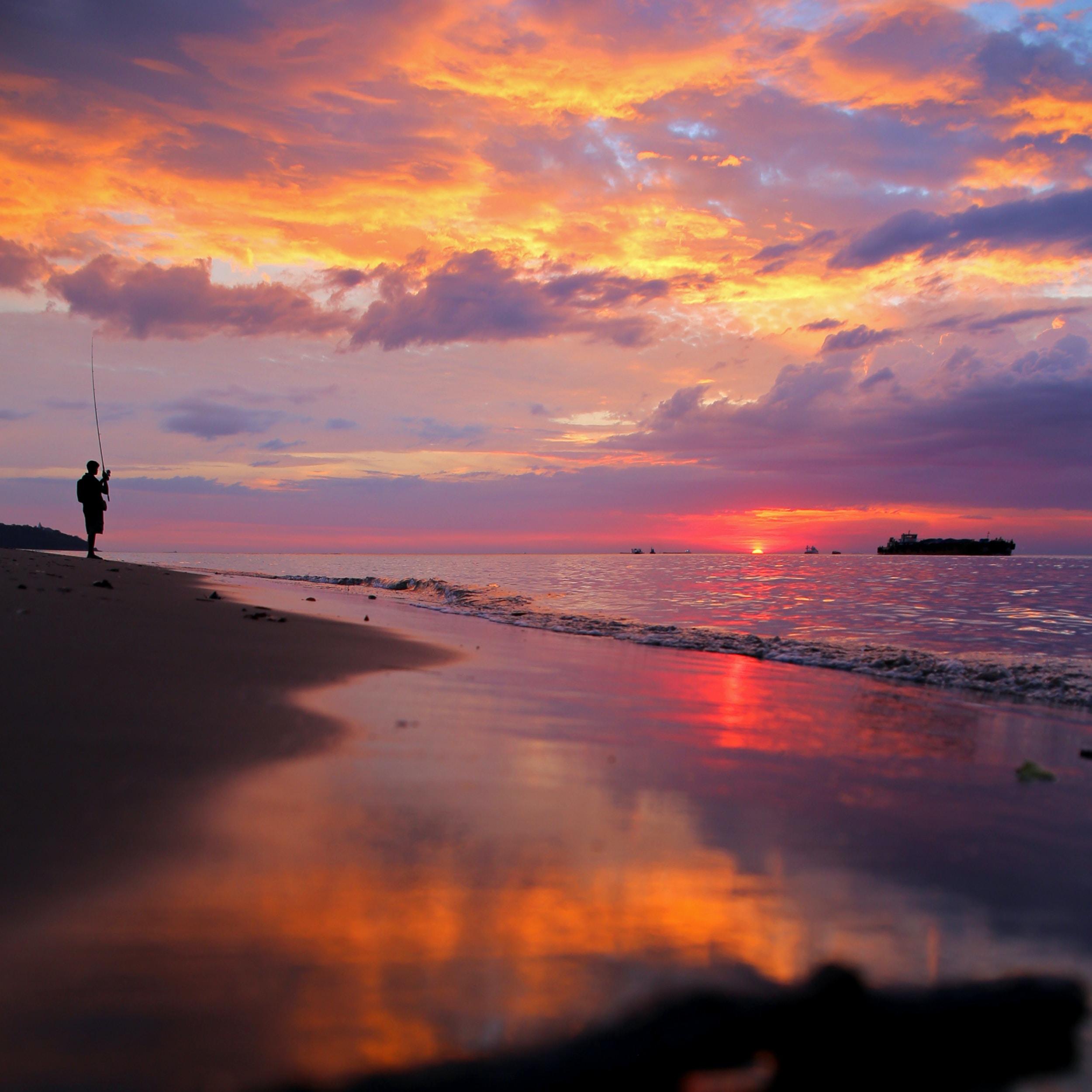 man standing on seashore during golden hour
