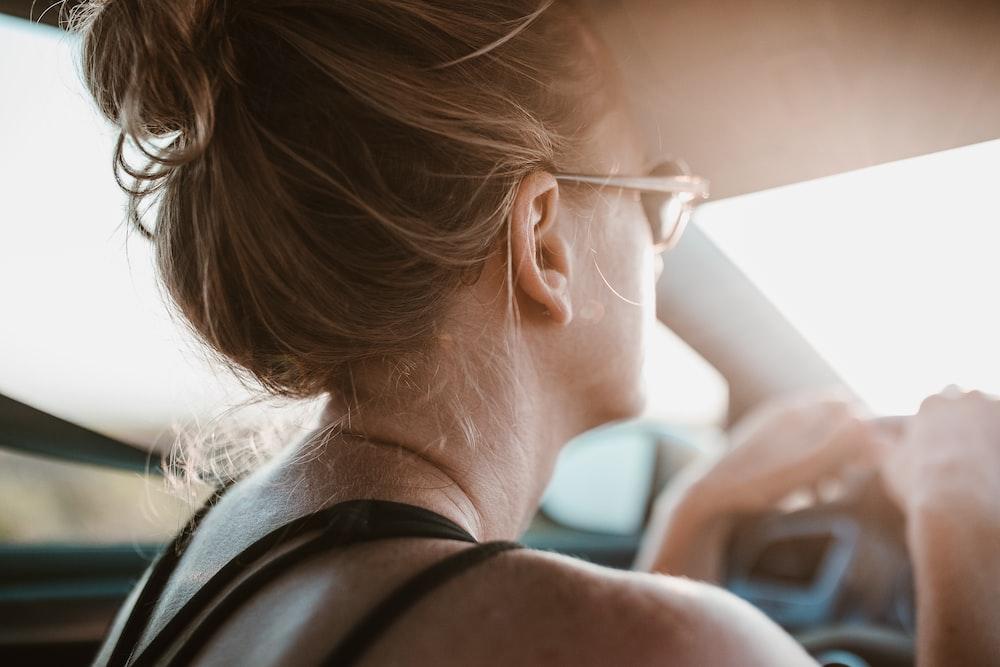 woman holding steering wheel inside vehicle