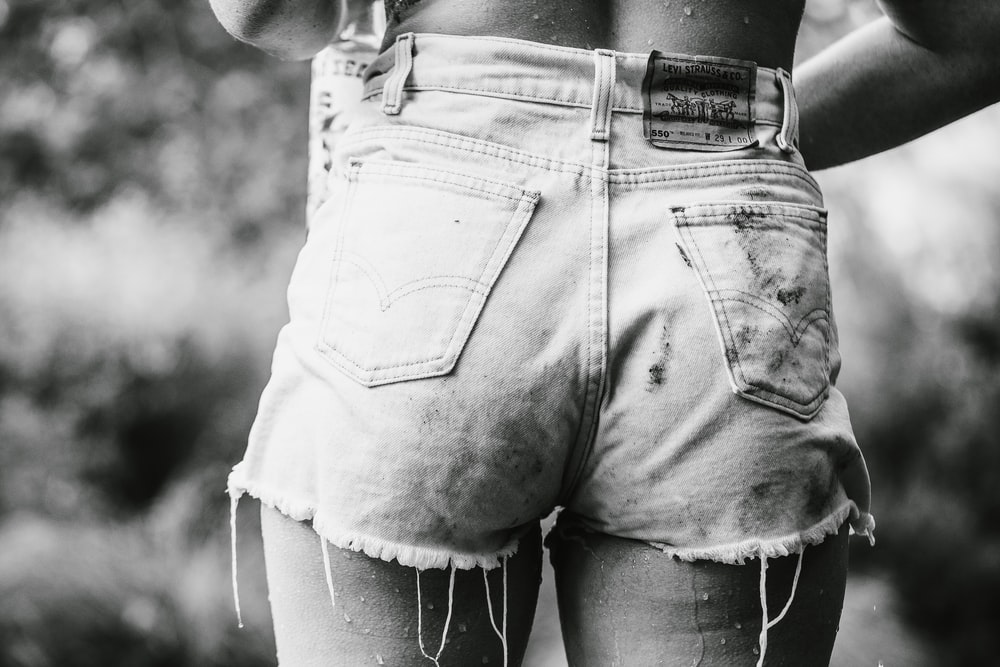 person wearing denim short-shorts in grayscale photography