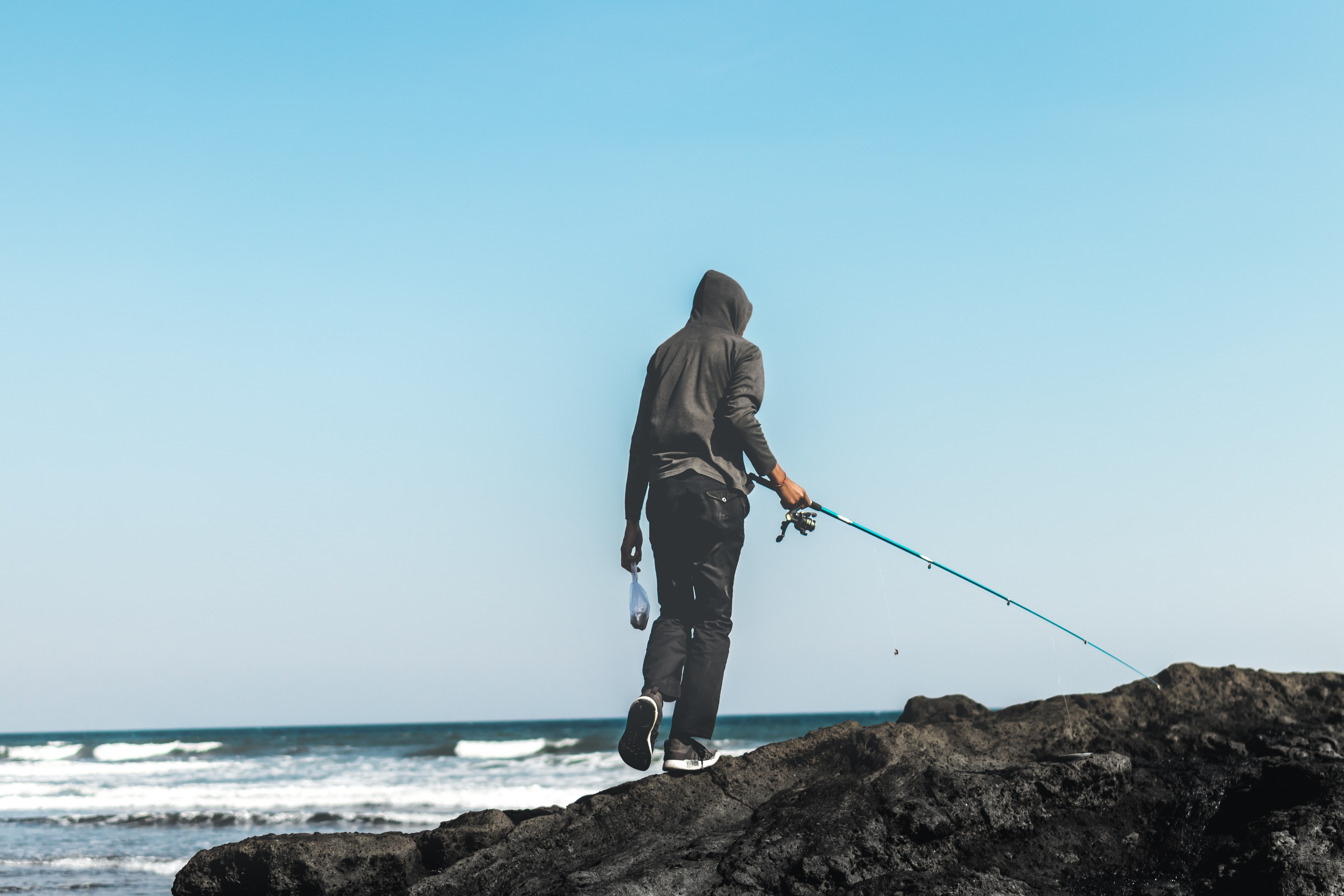 person standing on seacliff holding fishing rod