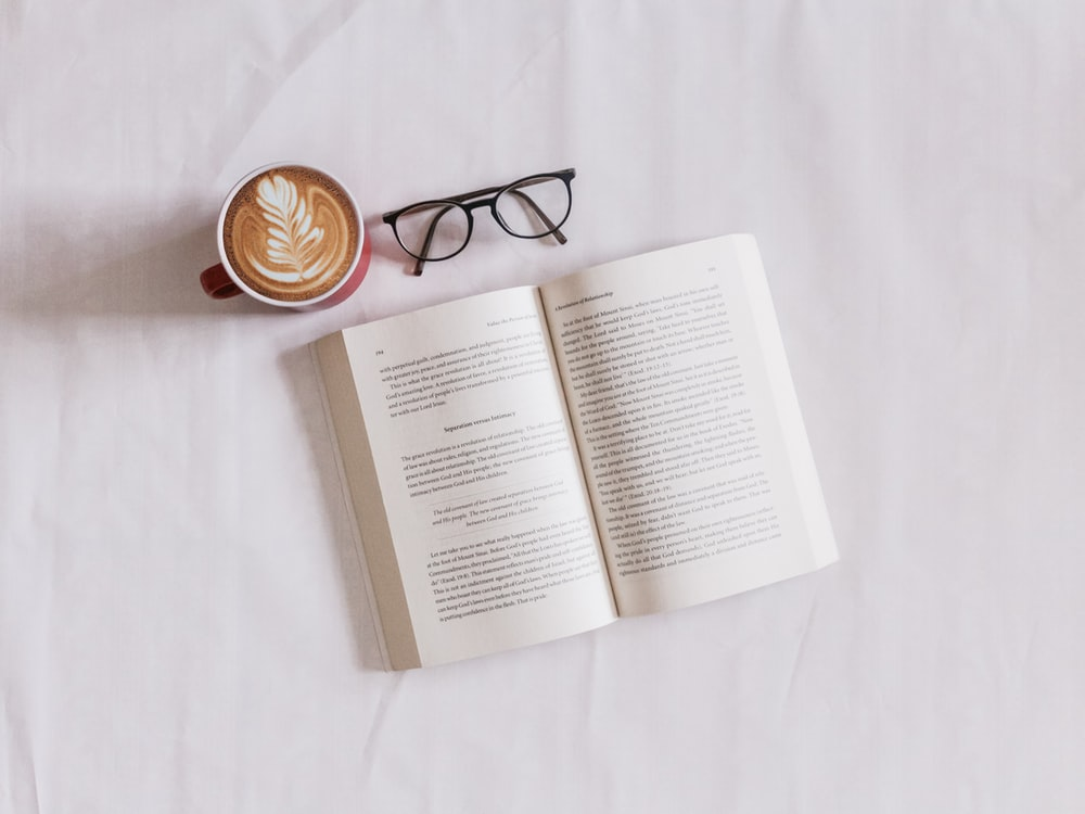 book near eyeglasses and cappuccino