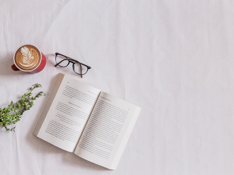 Libro sobre sábanas junto un café y unas gafas