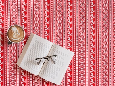 flat lay photography of eyeglasses on opened book frosty the snowman teams background