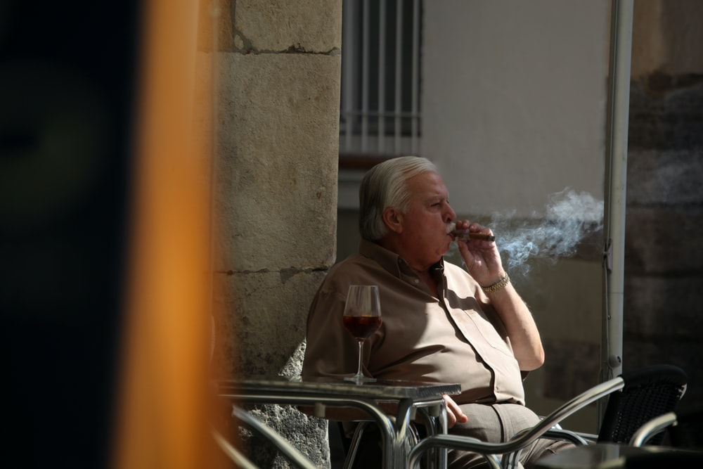 man sitting on chair holding tobacco