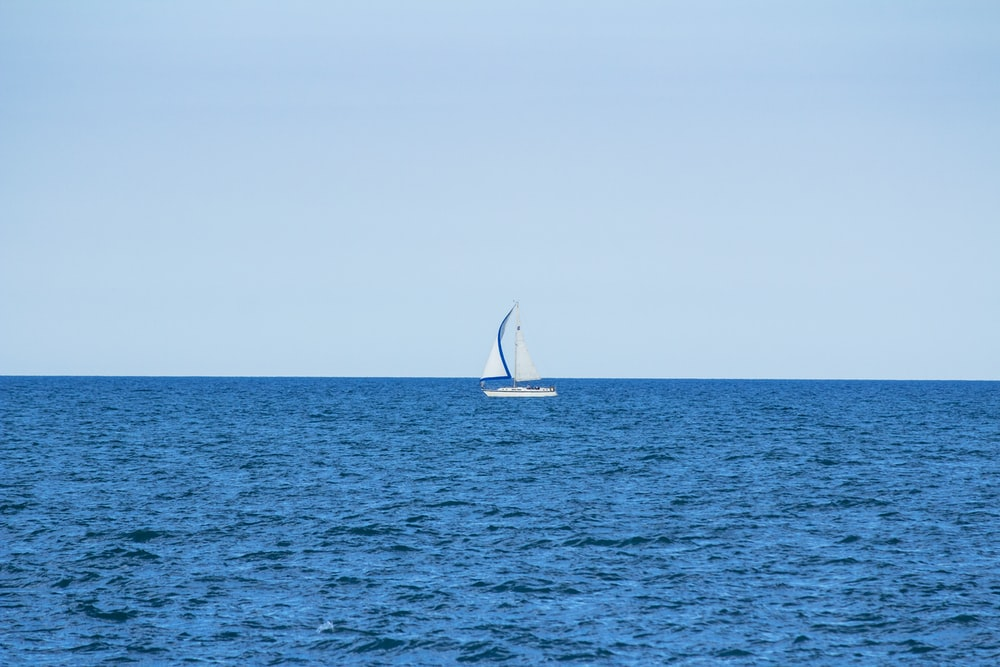 white sailboat in the middle of the ocean during day
