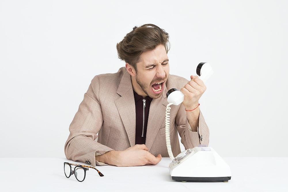 man holding telephone screaming