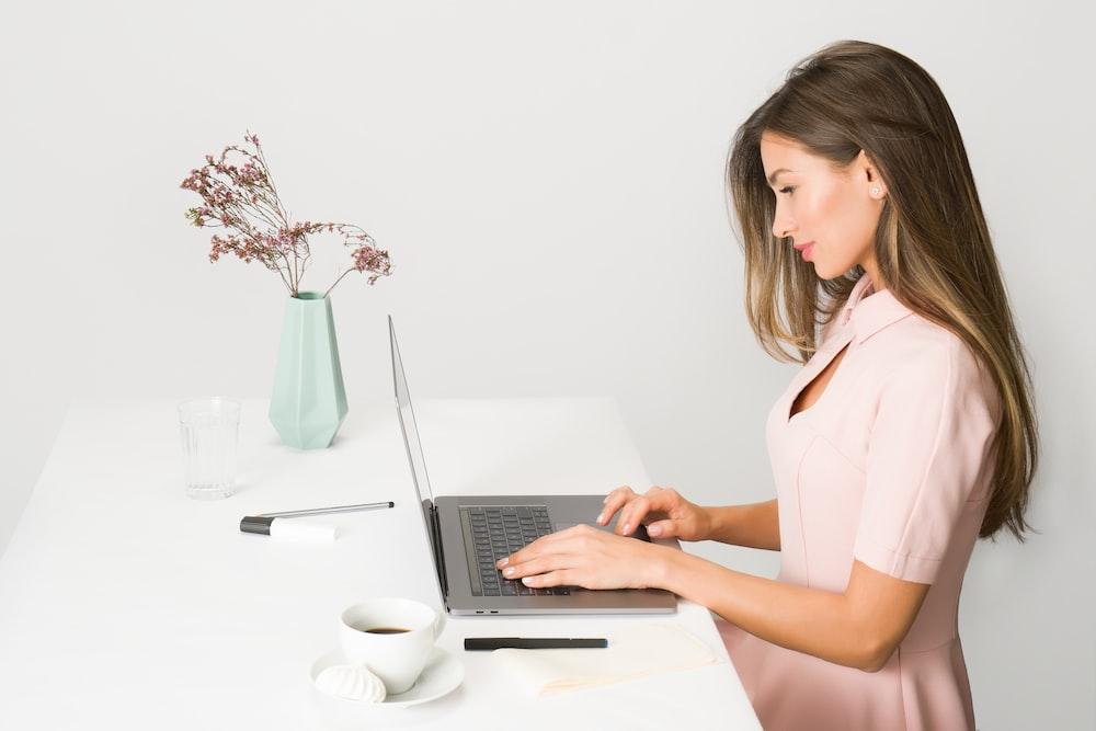 woman sitting while using laptop
