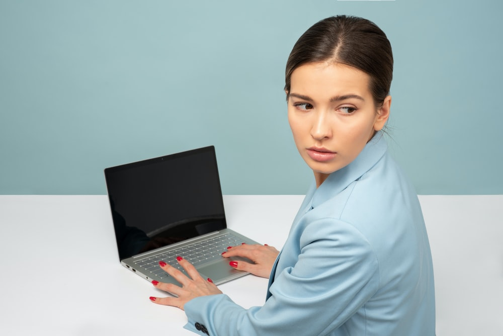 woman using laptop and looking side