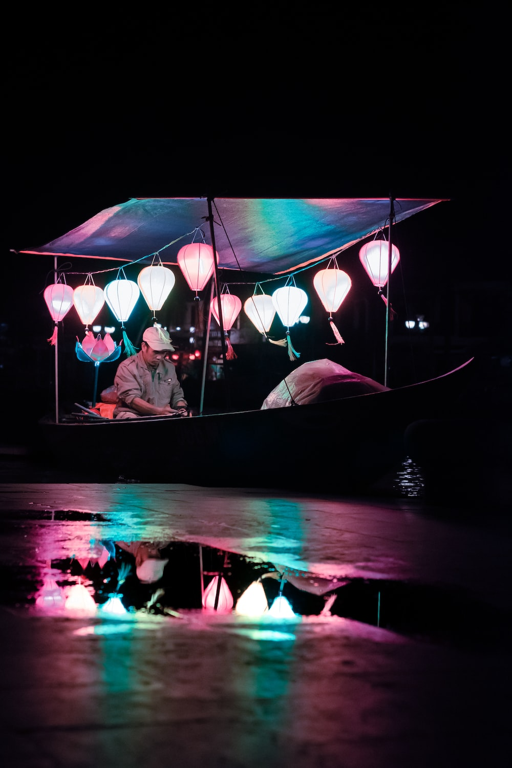 man riding boat with multicolored lanterns at night