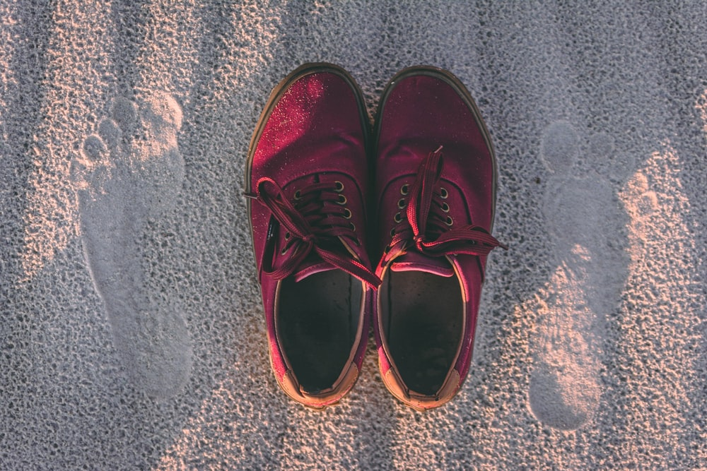 pair of red sneakers on sand