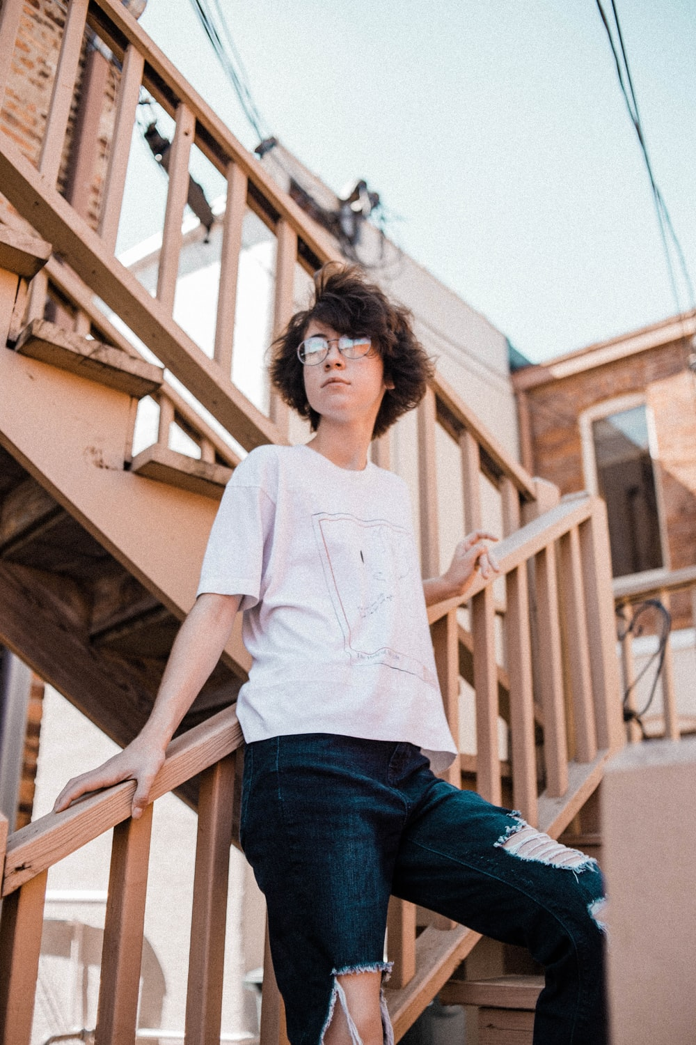 woman wearing white crew-neck t-shirt and distressed blue denim jeans standing on stairs during daytime