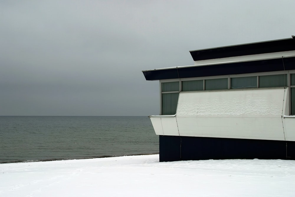 white and black house on snow seashore near body of water