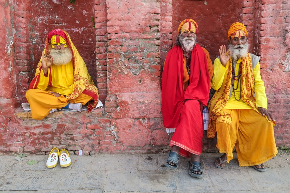 three religious men in yellow and red robes sitting by the red brink building