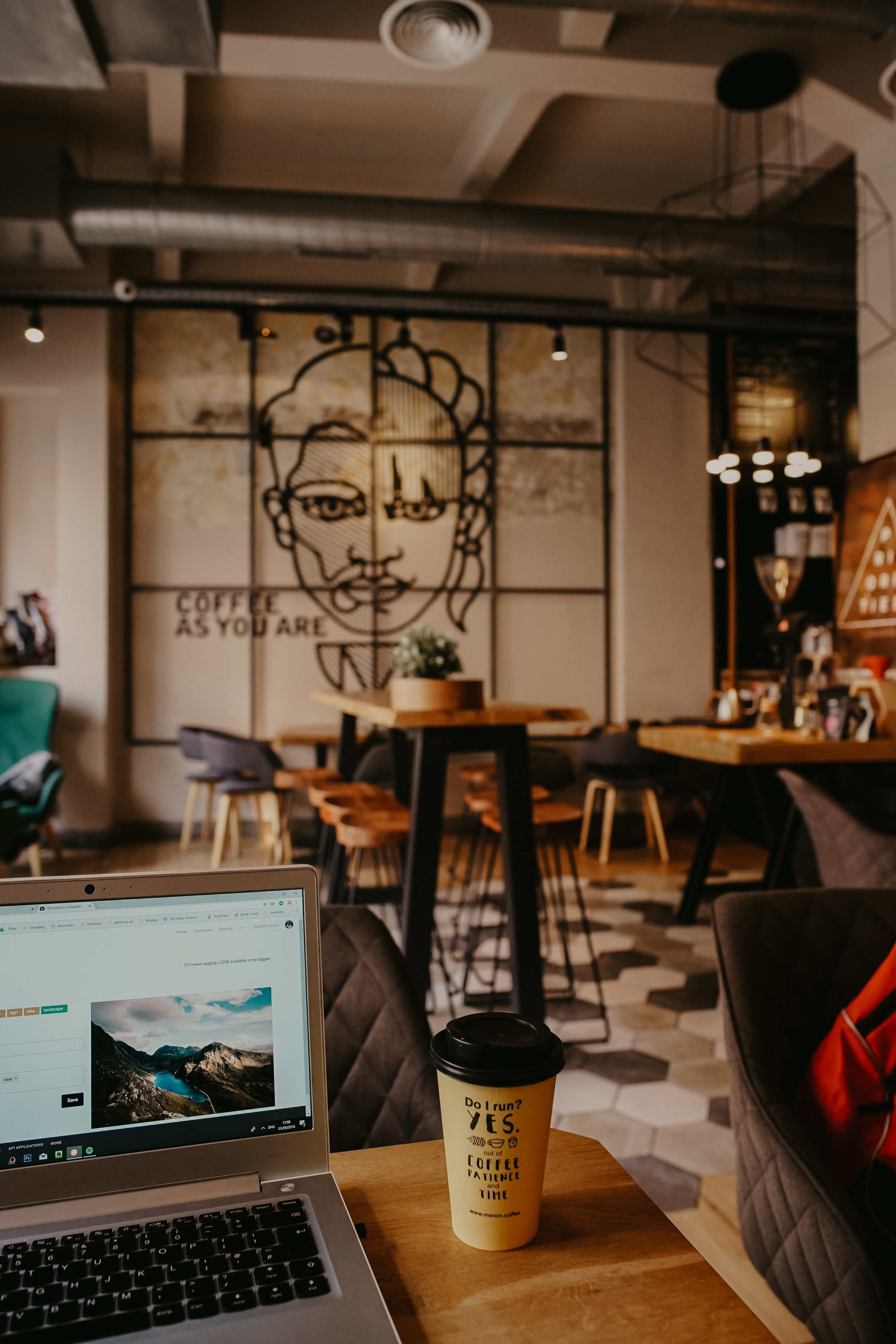 brown coffee cup beside laptop