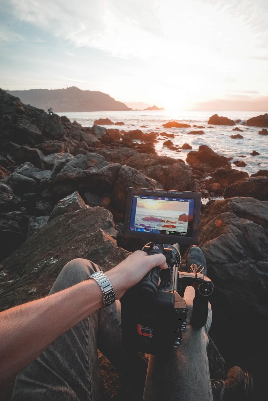 person taking photo of seashore using professional camera