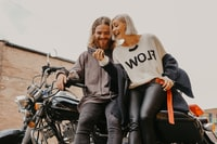 woman and man sitting on motorcycle while holding phone